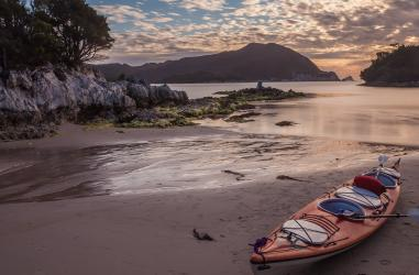 Bramble Cove sunset with kayaks in Southwest Tasmania